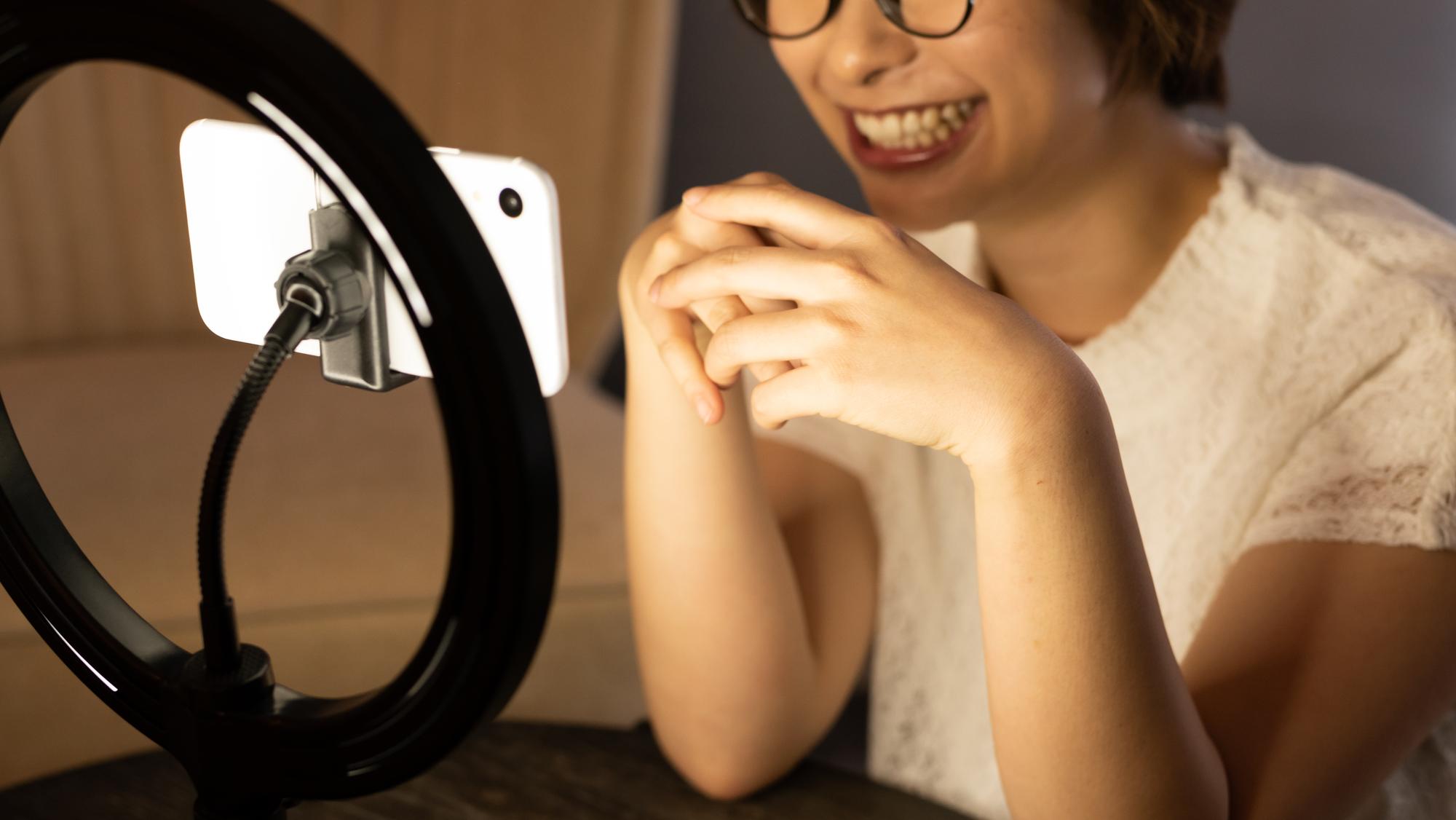 スマートフォンで動画配信をする女性