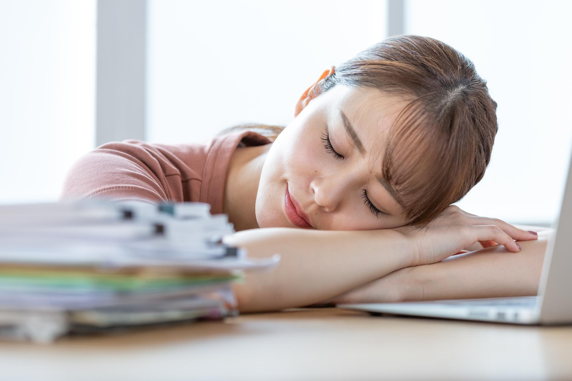 デスクの上で寝ている女性