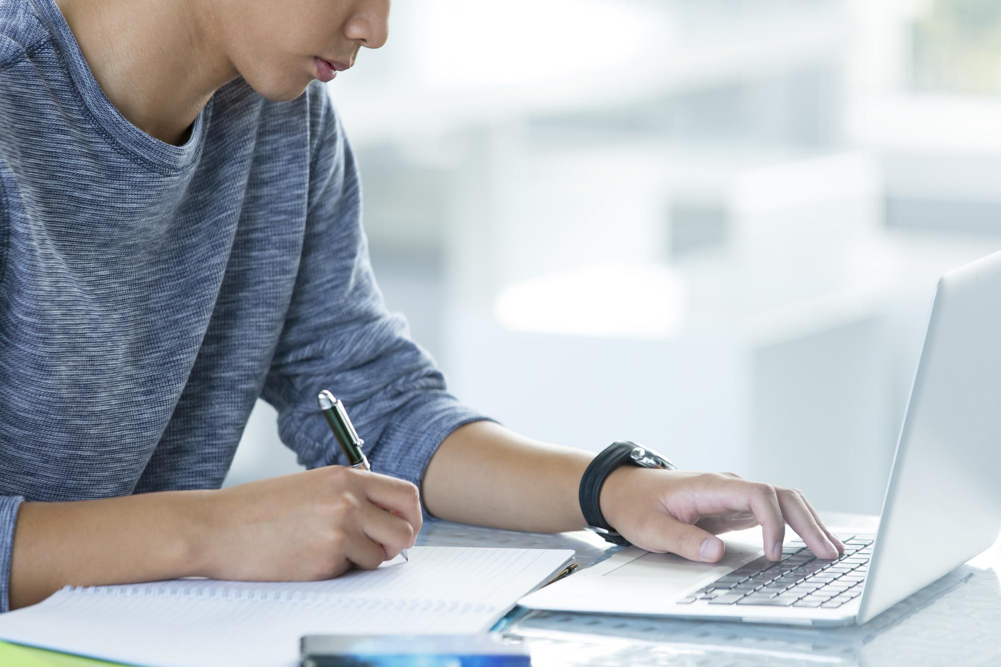 パソコンの前でメモを取っている男性