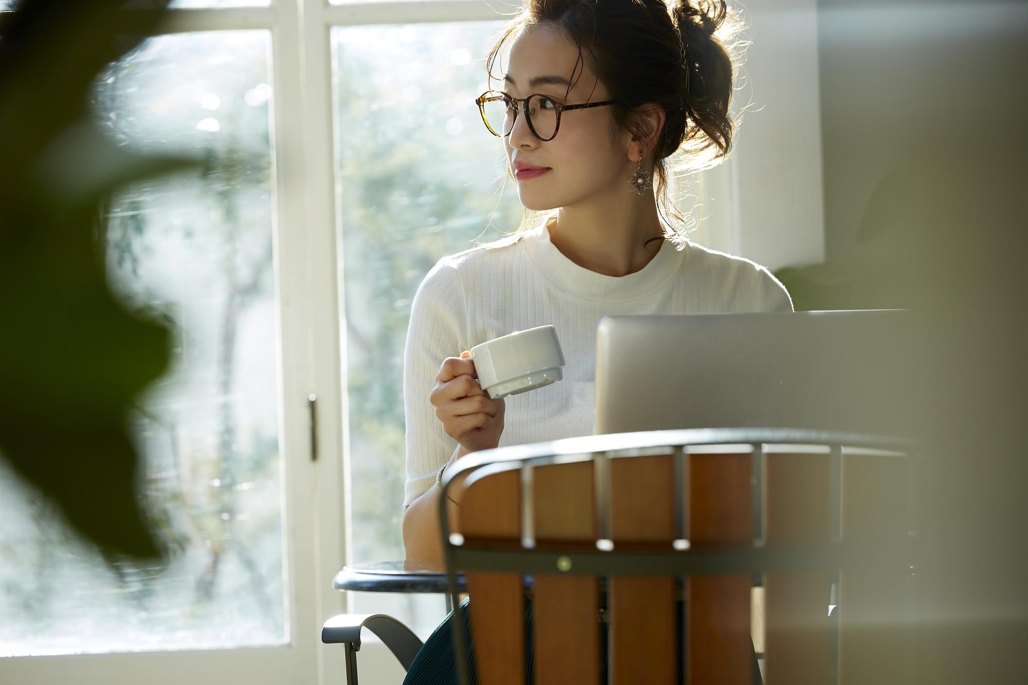 書類とカップを持って窓際に座っている女性