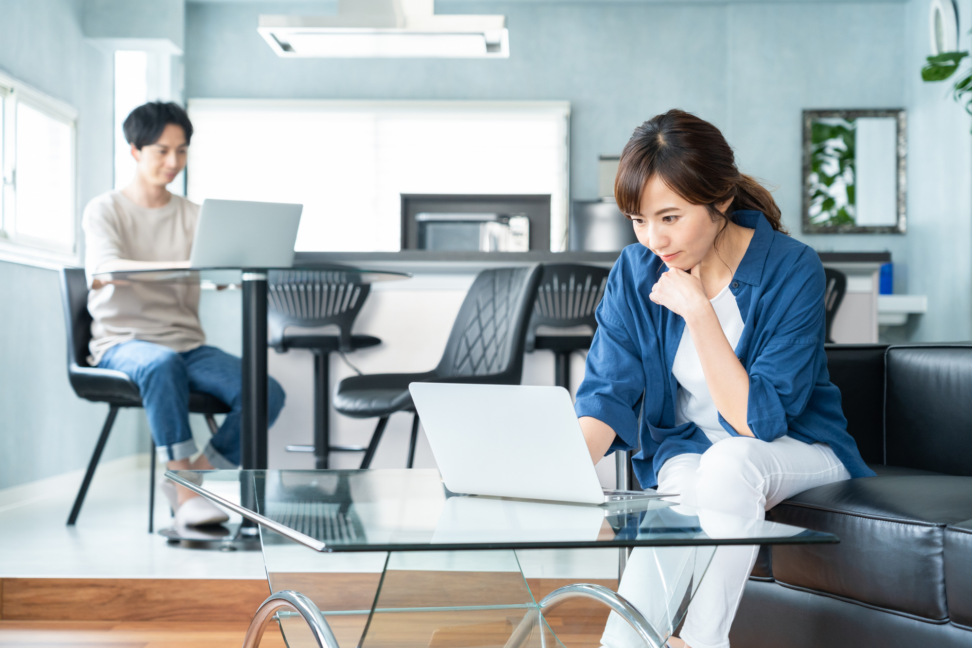 部屋の中でそれぞれ違うテーブルで仕事をしている夫婦