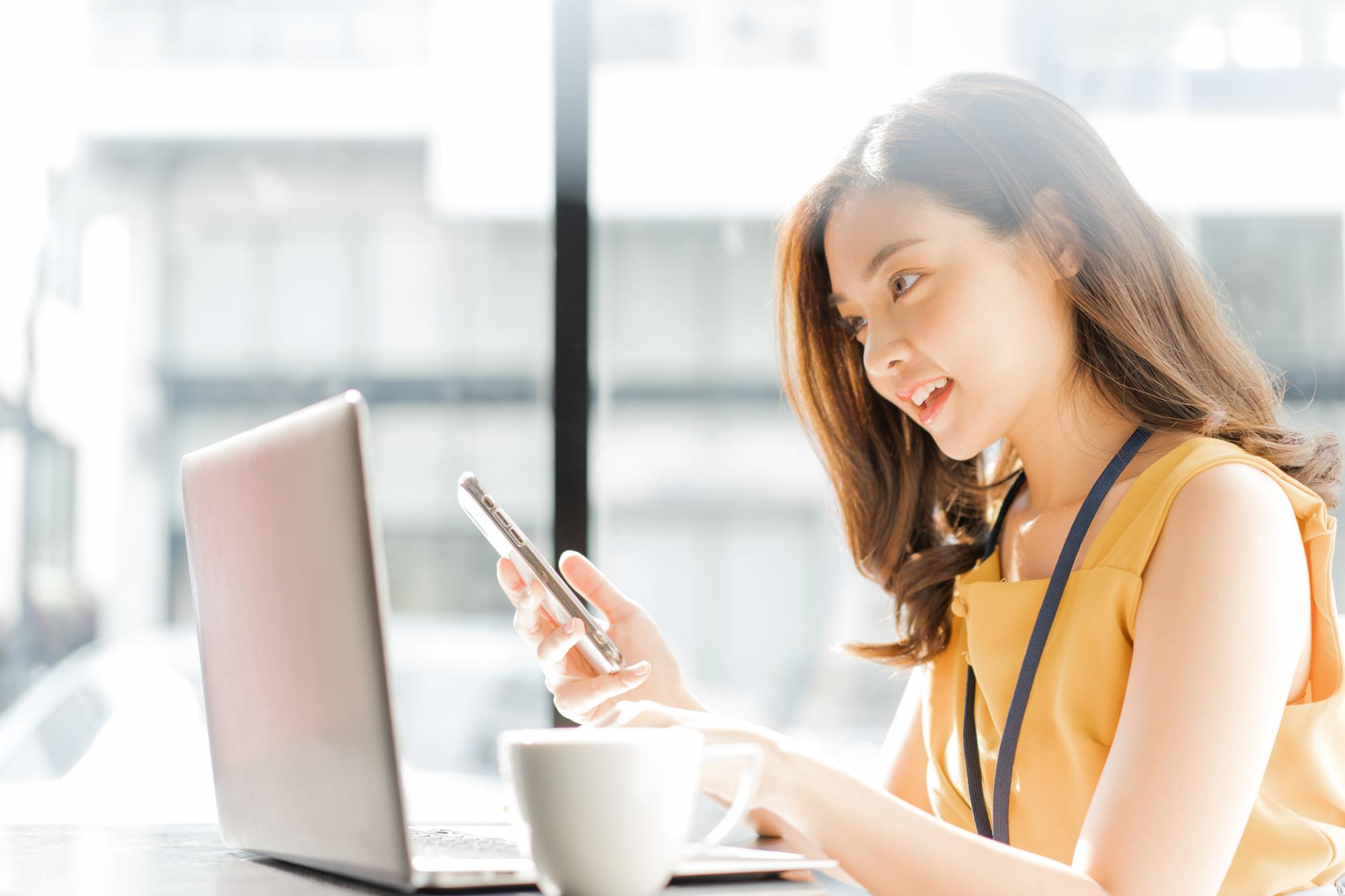 パソコンの前でスマホを使っている女性